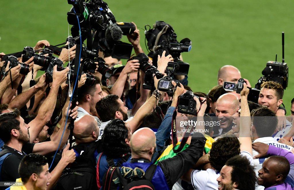 TOPSHOT - Real Madrid's French coach Zinedine Zidane and Real Madrid's Portuguese forward Cristiano Ronaldo celebrate winning the Liga title after the Spanish league football match Malaga CF vs Real Madrid CF at La Rosaleda stadium in Malaga on May 21, 2017. /