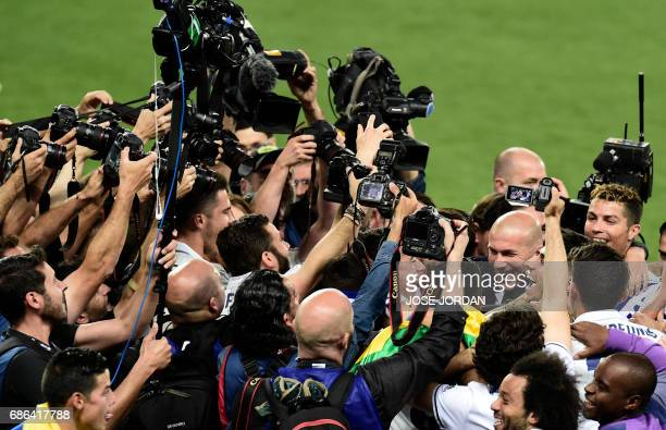 TOPSHOT Real Madrid's French coach Zinedine Zidane and Real Madrid's Portuguese forward Cristiano Ronaldo celebrate winning the Liga title after the...