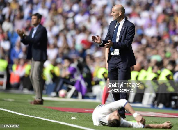 TOPSHOT Real Madrid's French coach Zinedine Zidane applauds as Real Madrid's Portuguese forward Cristiano Ronaldo lies in front of him during the...