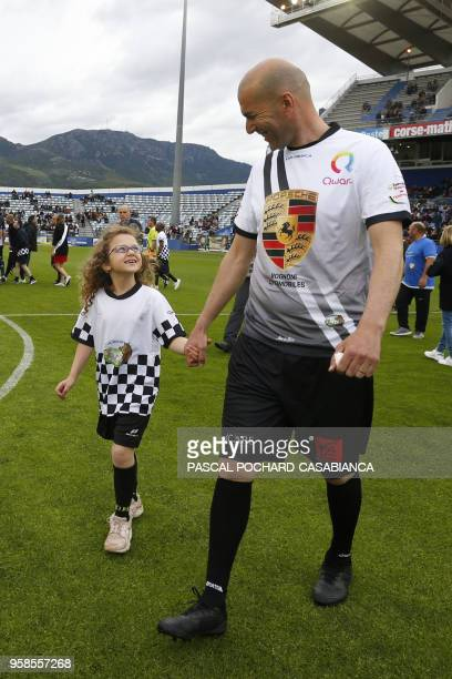 Real Madrid's French coach Zinedine Zidane arrives with a child before the start of the charity match organized by French football player Pascal...