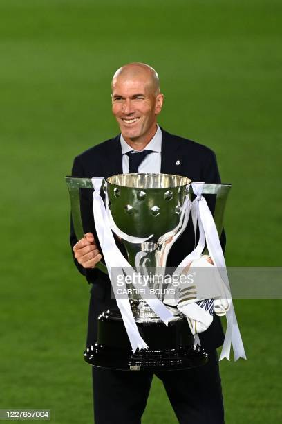 Real Madrid's French coach Zinedine Zidane celebrates winning the Liga title with the trophy after the Spanish League football match between Real...