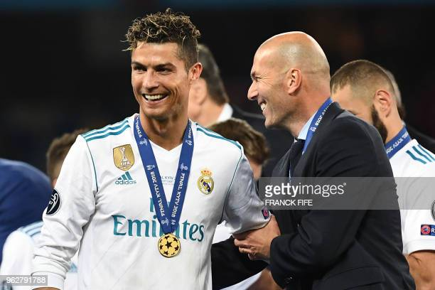 TOPSHOT Real Madrid's French coach Zinedine Zidane celebrates with Real Madrid's Portuguese forward Cristiano Ronaldo after winning the UEFA...