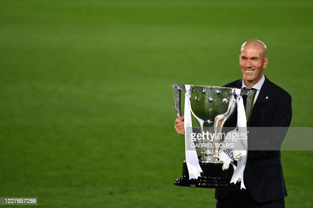 TOPSHOT Real Madrid's French coach Zinedine Zidane celebrates with the trophy after winning the Liga title after the Spanish League football match...