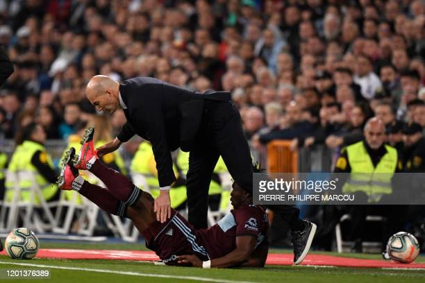 Real Madrid's French coach Zinedine Zidane collides with Celta Vigo's Ghanaian defender Joseph Aidoo during the Spanish league football match between...