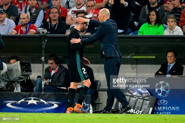 Real Madrid's French coach Zinedine Zidane congratulates Real Madrid's Spanish defender Dani Carvajal as he leaves the pitch during the UEFA...