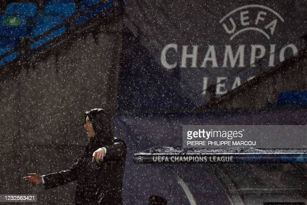 Real Madrid's French coach Zinedine Zidane gestures in the rain during the UEFA Champions League semi-final first leg football match between Real...