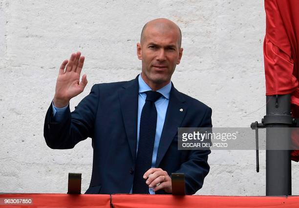 Real Madrid's French coach Zinedine Zidane greets supporters from the balcony of the headquarters of the regional government of Madrid at the Puerta...