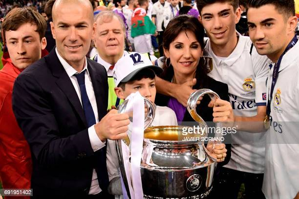Real Madrid's French coach Zinedine Zidane his wife Veronique and their children Enzo Theo and Elyaz hold the trophy after Real Madrid won the UEFA...
