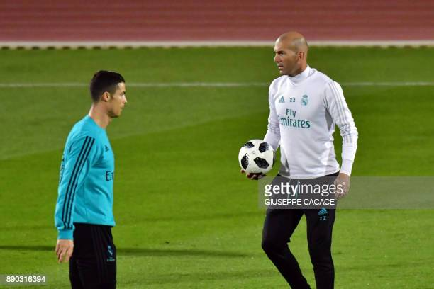 Real Madrid's French coach Zinedine Zidane holds the ball as he stands on the pitch with his Portuguese forward Cristiano Ronaldo during a training...