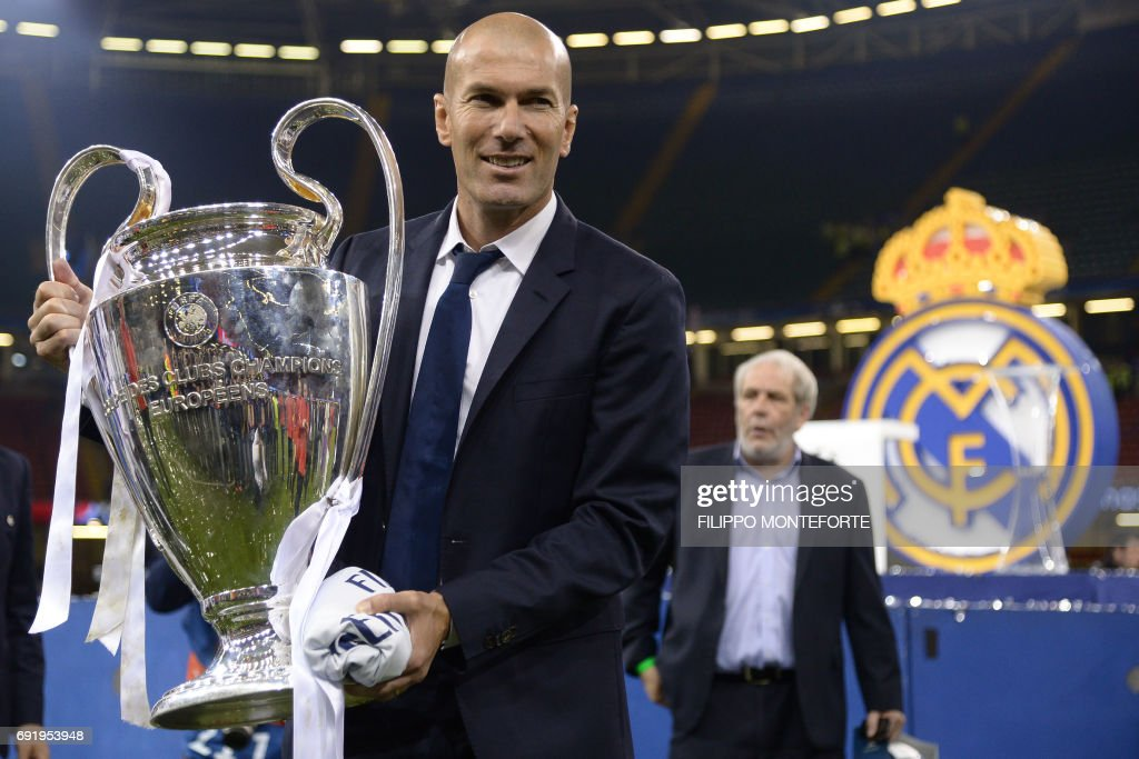 Real Madrid's French coach Zinedine Zidane holds the trophy after Real Madrid won the UEFA Champions League final football match between Juventus and Real Madrid at The Principality Stadium in Cardiff, south Wales, on June 3, 2017. / AFP PHOTO / Filippo MONTEFORTE
