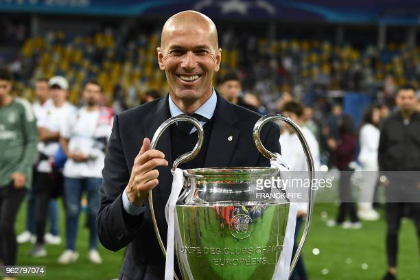 Real Madrid's French coach Zinedine Zidane holds the trophy as he celebrates winning the UEFA Champions League final football match between Liverpool...