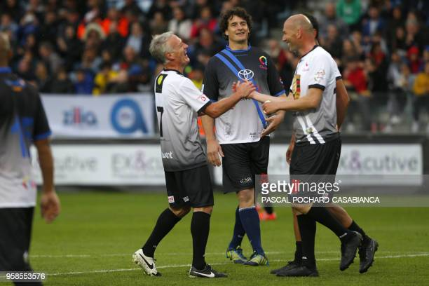 Real Madrid's French coach Zinedine Zidane laughs with France's coach Didier Deschamps during the charity match organized by French football player...