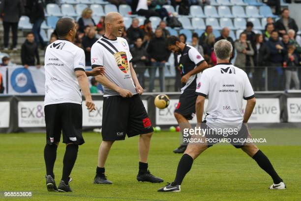 Real Madrid's French coach Zinedine Zidane laughs with France's coach Didier Deschamps during the warmup before the charity match organized by French...