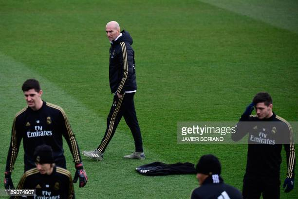 Real Madrid's French coach Zinedine Zidane looks at his players during a training session at the Real Madrid City sports facilities in Madrid on...