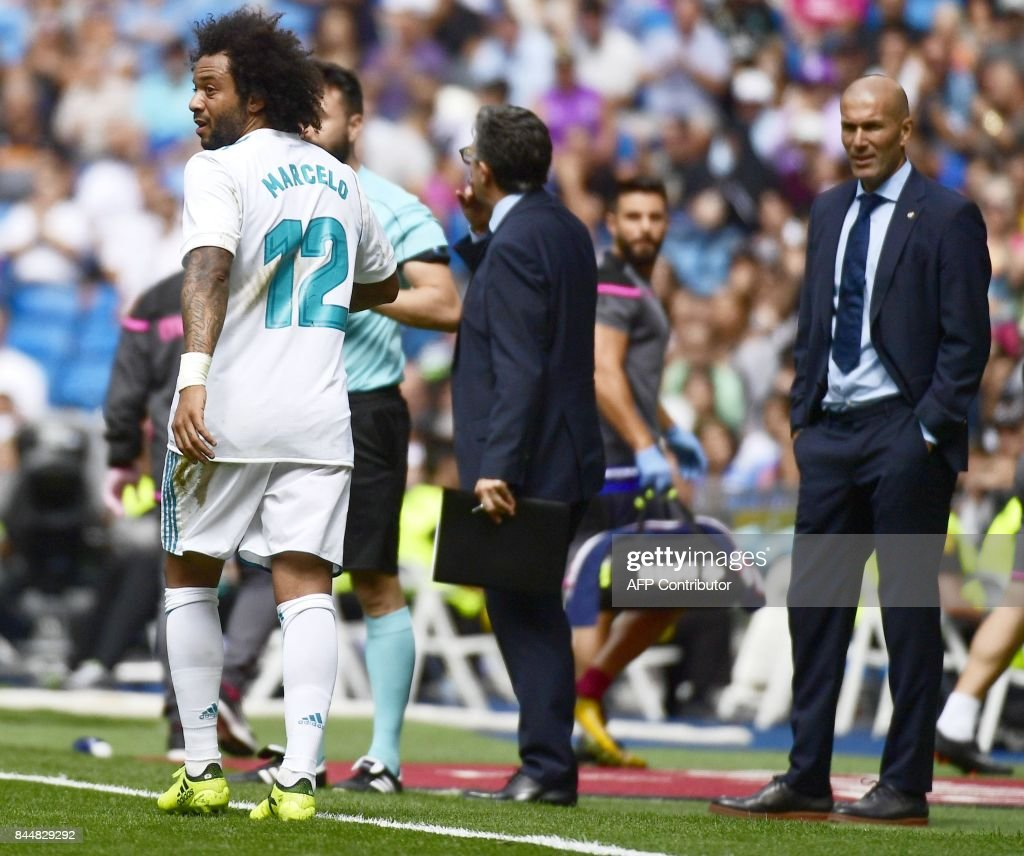 Real Madrid's French coach Zinedine Zidane (R) looks at Real Madrid's Brazilian defender Marcelo leaving the field after receiving a red card during the Spanish Liga football match Real Madrid vs Levante at the Santiago Bernabeu stadium in Madrid on September 9, 2017. /