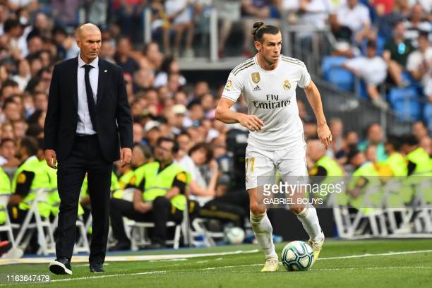 Real Madrid's French coach Zinedine Zidane looks at Real Madrid's Welsh forward Gareth Bale during the Spanish League football match between Real...