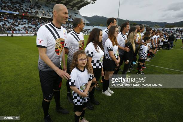 Real Madrid's French coach Zinedine Zidane poses with a child before the start of the charity match organized by French football player Pascal Olmeta...