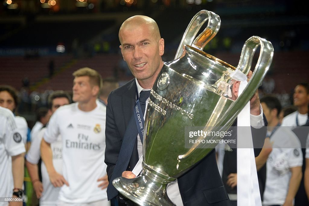 Real Madrid's French coach Zinedine Zidane poses with the trophy after Real Madrid won the UEFA Champions League final football match between Real Madrid and Atletico Madrid at San Siro Stadium in Milan, on May 28, 2016. / AFP / Filippo MONTEFORTE