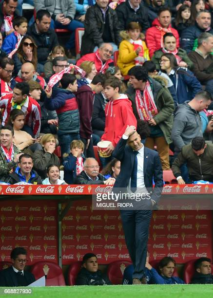 Real Madrid's French coach Zinedine Zidane reacts after the second goal scored by Sporting Gijon's midfielder Mikel Vesga during the Spanish league...