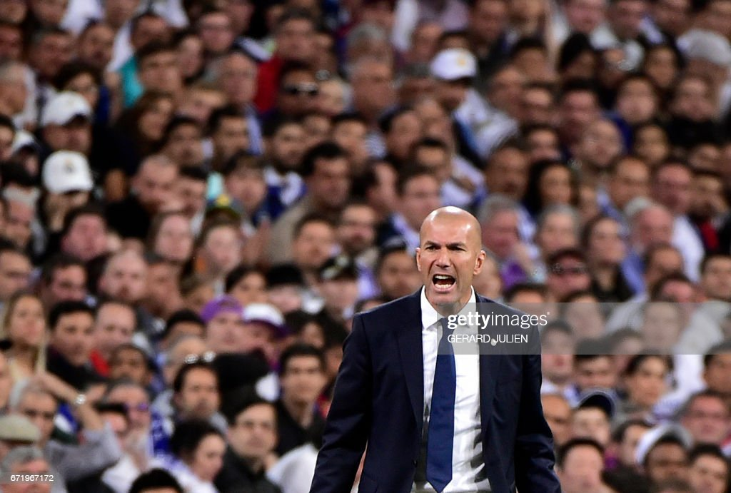 TOPSHOT - Real Madrid's French coach Zinedine Zidane shouts on the sideline during the Spanish league Clasico football match Real Madrid CF vs FC Barcelona at the Santiago Bernabeu stadium in Madrid on April 23, 2017.