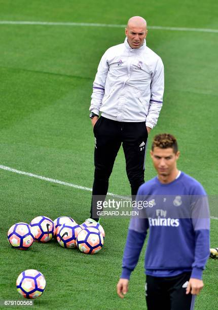 Real Madrid's French coach Zinedine Zidane stands on the pitch with Real Madrid's Portuguese forward Cristiano Ronaldo in foreground during a...