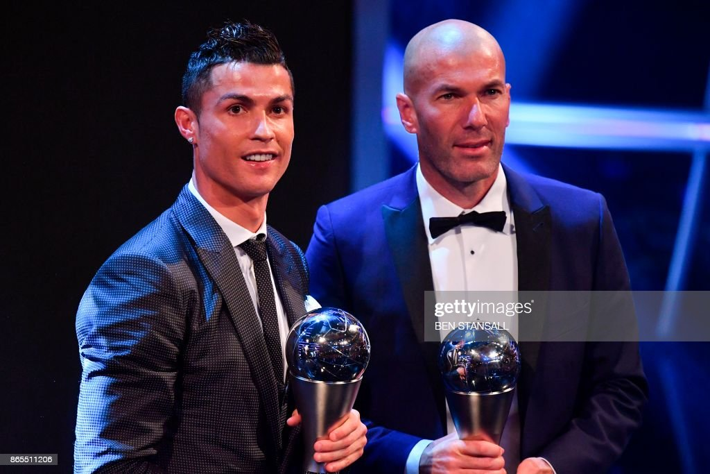 TOPSHOT - Real Madrid's French coach Zinedine Zidane (R) stands with his trophy for winning The Best FIFA Men's Coach of 2017 Award alongside Real Madrid and Portugal forward Cristiano Ronaldo, with his trophy for winning The Best FIFA Men's Player of 2017 Award during The Best FIFA Football Awards ceremony, on October 23, 2017 in London.