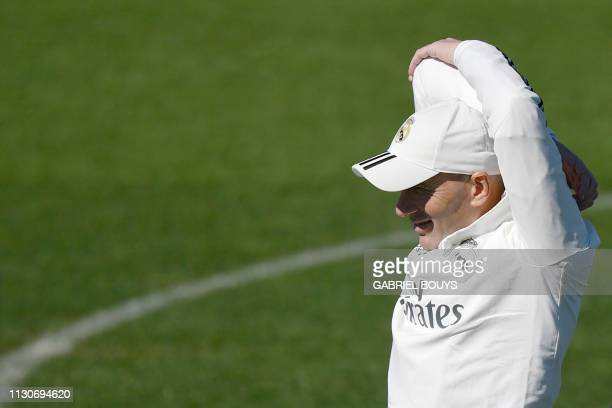 Real Madrid's French coach Zinedine Zidane stretches during a training session at the Valdebebas training facilities in Madrid on March 15, 2019.