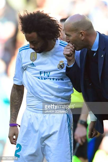Real Madrid's French coach Zinedine Zidane talks to Real Madrid's Brazilian defender Marcelo during the Spanish League 'Clasico' football match Real...