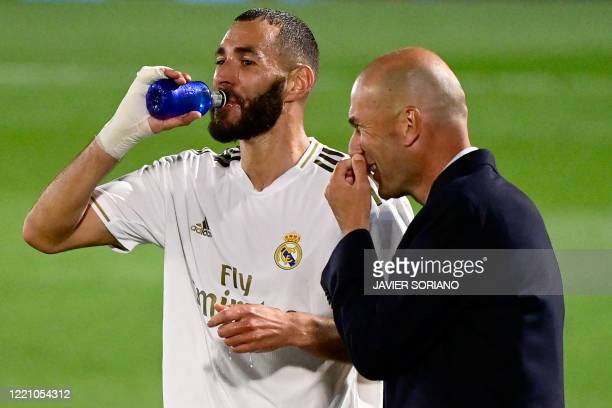 Real Madrid's French coach Zinedine Zidane talks with Real Madrid's French forward Karim Benzema during the Spanish league football match between...
