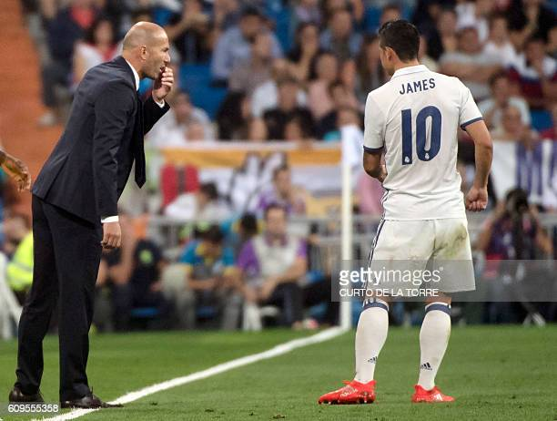 Real Madrid's French coach Zinedine Zidane talks with Real Madrid's Colombian midfielder James Rodriguez during the Spanish league football match...