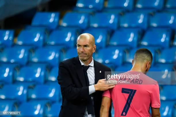 Real Madrid's French coach Zinedine Zidane taps Real Madrid's Belgian forward Eden Hazard as he leaves the pitch after being substituted off during...