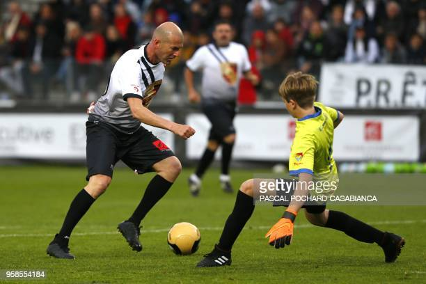 TOPSHOT Real Madrid's French coach Zinedine Zidane vies with Lisandru Olmeta during the charity match organized by French football player Pascal...