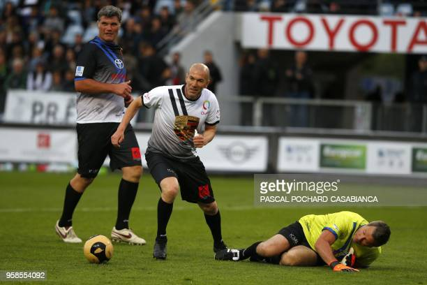 Real Madrid's French coach Zinedine Zidane vies with Pascal Olmeta during the charity match organized by French football player Pascal Olmeta for his...