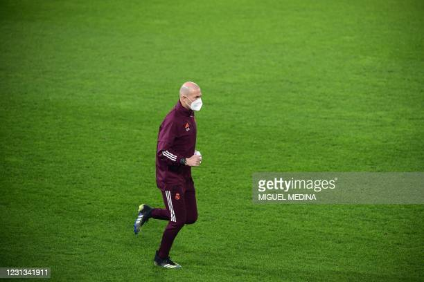 Real Madrid's French coach Zinedine Zidane wears a face mask as he runs during a training session on February 23, 2021 at the Atleti Azzurri d'Italia...