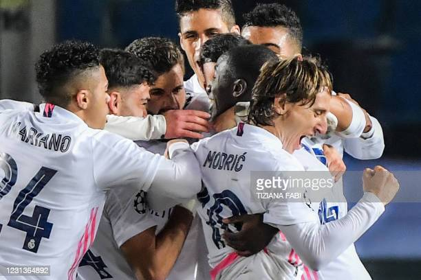 Real Madrid's French defender Ferland Mendy celebrates with teammates after opening the scoring during the UEFA Champions League round of 16 first...