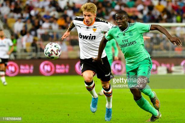 Real Madrid's French defender Ferland Mendy vies for the ball with Valencia's Danish midfielder Daniel Wass during the Spanish Super Cup semi final...