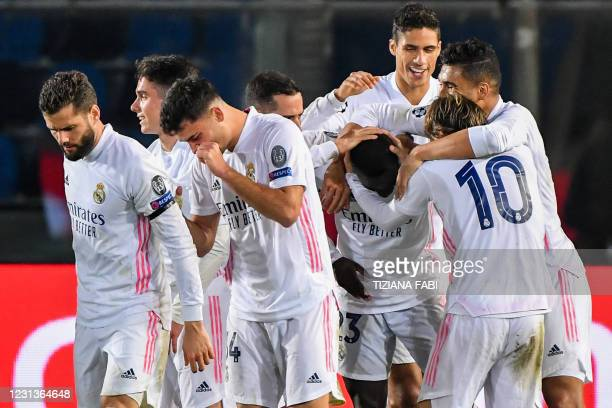Real Madrid's French defender Raphael Varane and Real Madrid players congratulate Real Madrid's French defender Ferland Mendy after he opened the...