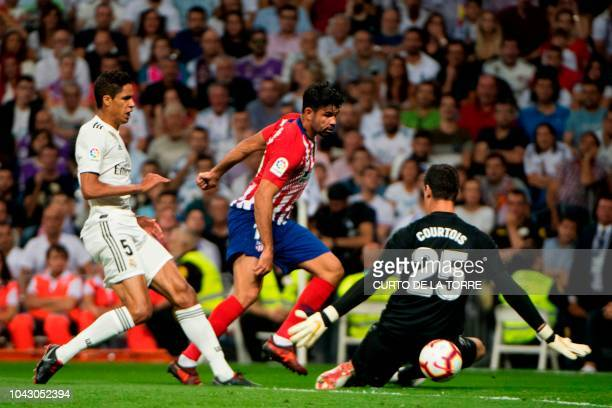 Real Madrid's French defender Raphael Varane and Real Madrid's Belgian goalkeeper Thibaut Courtois vie with Atletico Madrid's Spanish forward Diego...