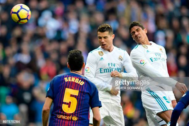 Real Madrid's French defender Raphael Varane and Real Madrid's Portuguese forward Cristiano Ronaldo jump for the ball during the Spanish League...