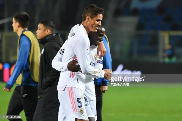 Real Madrid's French defender Raphael Varane and Real Madrid's French defender Ferland Mendy react at the end of the UEFA Champions League round of...