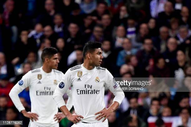 Real Madrid's French defender Raphael Varane and Real Madrid's Brazilian midfielder Casemiro react during the UEFA Champions League round of 16...
