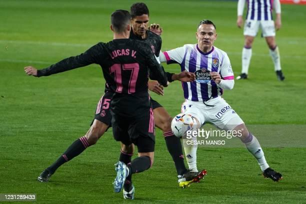 Real Madrid's French defender Raphael Varane and Real Madrid's Spanish midfielder Lucas Vazquez challenge Real Valladolid's Spanish midfielder Roque...