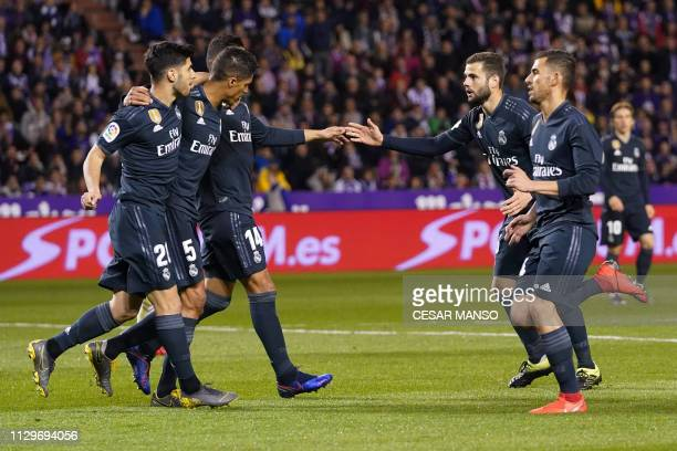 Real Madrid's French defender Raphael Varane celebrates his goal with teammates during the Spanish league football match between Real Valladolid FC...