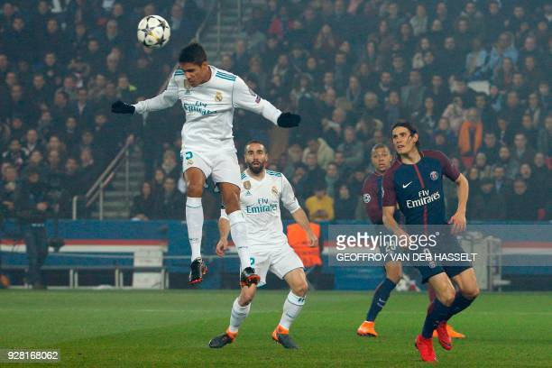 Real Madrid's French defender Raphael Varane heads the ball during the UEFA Champions League round of 16 second leg football match between Paris...