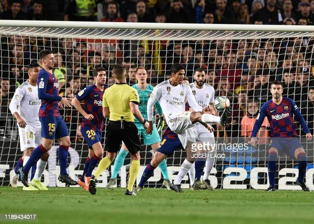 Real Madrid's French defender Raphael Varane kicks the ball during the El Clasico Spanish League football match between Barcelona FC and Real Madrid...
