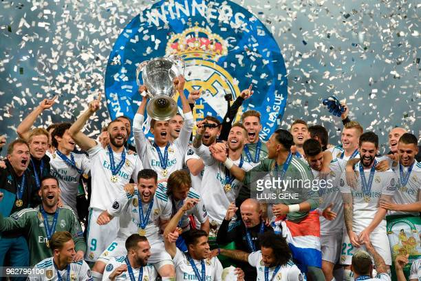 Real Madrid's French defender Raphael Varane lifts the trophy after winning the UEFA Champions League final football match between Liverpool and Real...