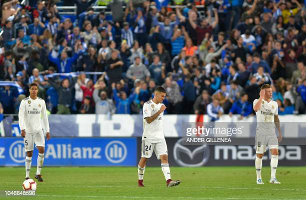 Real Madrid's French defender Raphael Varane Spanish midfielder Daniel Ceballos and German midfielder Toni Kroos gesture after Alaves scored a goal...