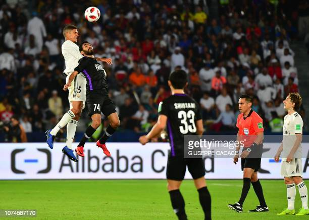 Real Madrid's French defender Raphael Varane vies for the header with AlAin's midfielder Hussein elShahat during the Final match in the FIFA Club...