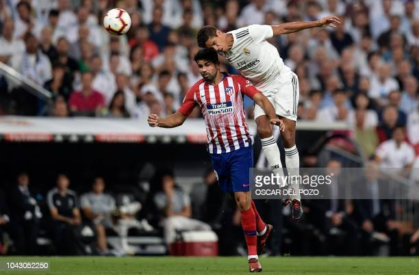 Real Madrid's French defender Raphael Varane vies with Atletico Madrid's Spanish forward Diego Costa during the Spanish league football match between...