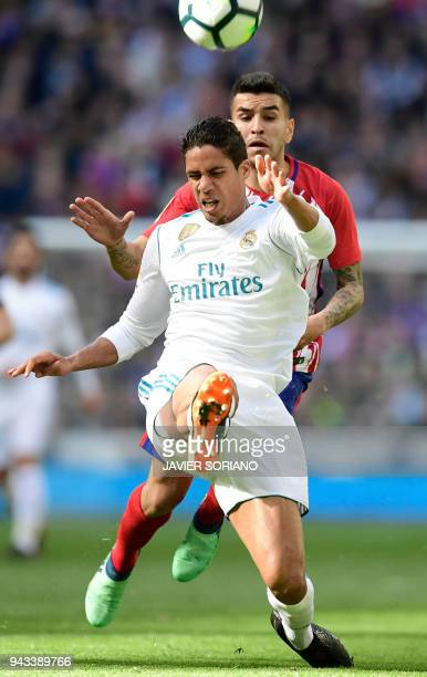 Real Madrid's French defender Raphael Varane vies with Atletico Madrid's Argentinian forward Angel Correa during the Spanish league football match...